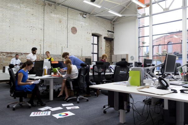 Photo of a large office space with people working on computers and office desks.